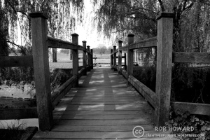 a black and white image of a wooden bridge