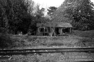 black and white shot of a dilapidated building by a railway track