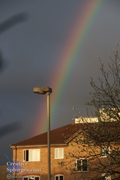 rainbow over housing estate, streetlight in the foreground
