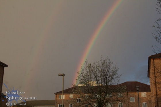 a double rainbow above a housing estate