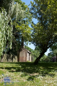 photograph of a small building amongst trees