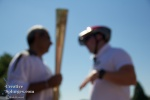 One of the torch relay team 'relays' instructions to the torchbearer. Although this shot is out of focus, I quite like the effect.