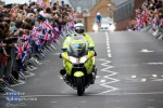 A police bike leads the way for another competitor.