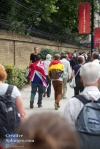 Two friends, one draped in the UK flag, the other in the German flag, walk home.